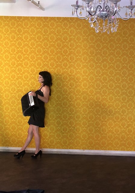 musician-onah-indigo-leans-against-yellow-wall-at-drip-studios
