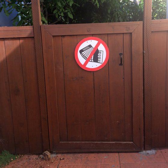 noaccordion-street-sign-black-red-white-on-gate